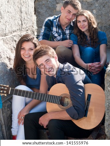 Four happy teenage friends boys and girls playing guitar