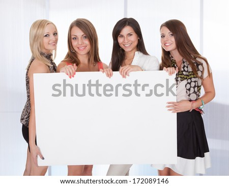 Four Happy Young Women Holding Blank Placard - stock photo