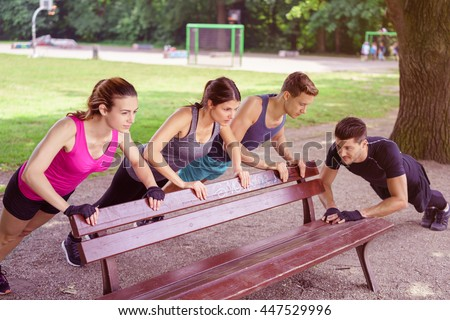 Four healthy fit young people working out in a park using a wooden bench as a prop and support for their exercises - stock photo
