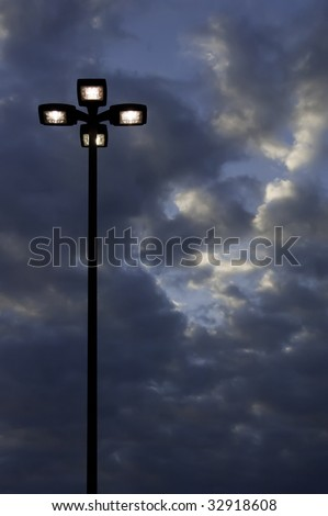 Four high outdoor lights against evening sky - stock photo