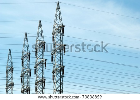 four high voltage towers against a blue sky