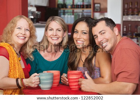 Four Hispanic and Caucasian friends at table in cafe