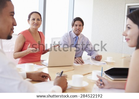 Four Hispanic Businesspeople Having Meeting In Boardroom