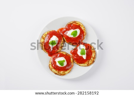 four hot pancakes with strawberry jam on white plate - stock photo