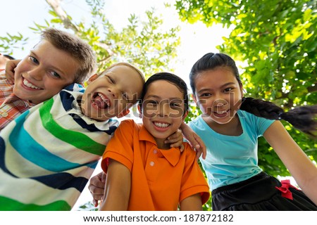 Four hugging and smiling children, view from below - stock photo