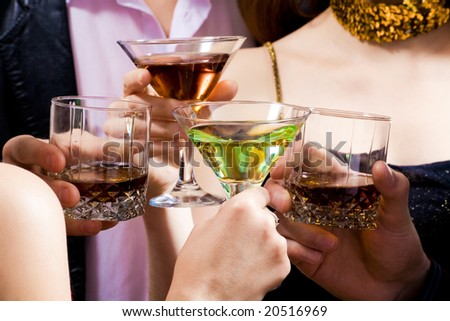 Four human hands holding the glasses of cocktails making a toast - stock photo