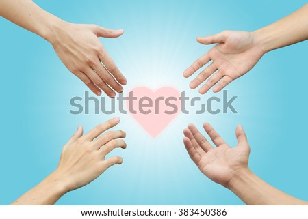 four human hands try to reaching heart shape on blur blue teal color background with sun rays: collaborate working together concept:love,trust,hope of humanity idea:helping hands conceptual - stock photo