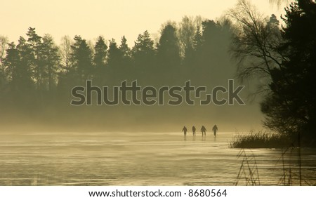 four ice skaters on frozen winter lake on january afternoon - stock photo