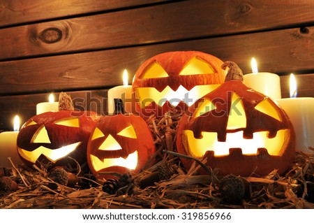 four illuminated halloween pumpkins on straw in front of old weathered wooden board in candlelight - stock photo