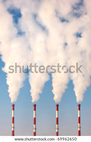 four industrial chimneys polluting - stock photo