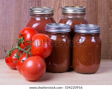 Four jars of tomato sauce with fresh tomatoes - stock photo