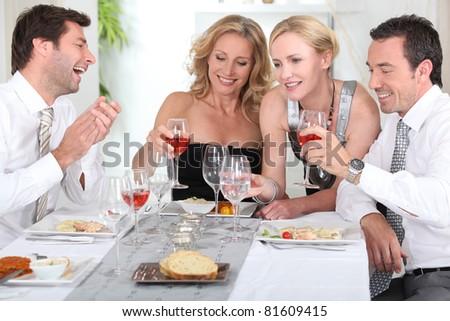 Four joyful people at the start of a posh dinner. - stock photo