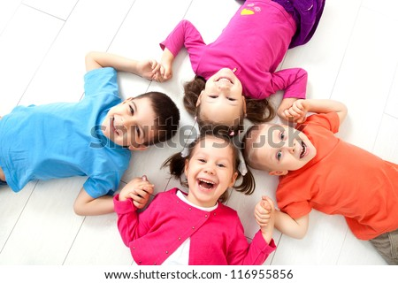 Four kids are on the floor together. Top view - stock photo