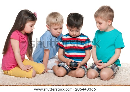 Four kids are playing with a gadget on the white carpet