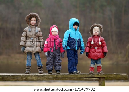 Four kids having fun on early spring or late autumn - stock photo