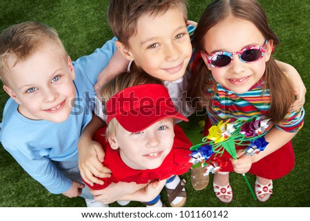 Four kids looking up, girl wearing sunglasses and holding a vane - stock photo