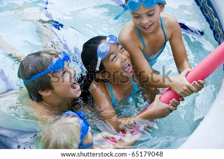 Four kids playing tug of war with pool toy, 7 to 9 years - stock photo