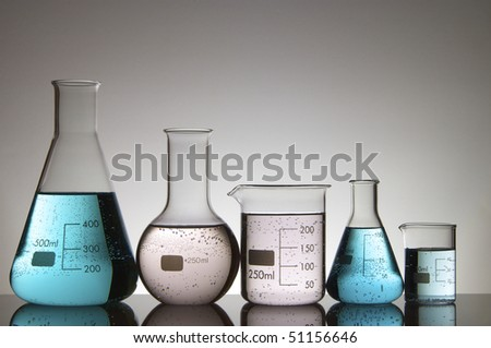 four laboratory flasks with liquid and a white background