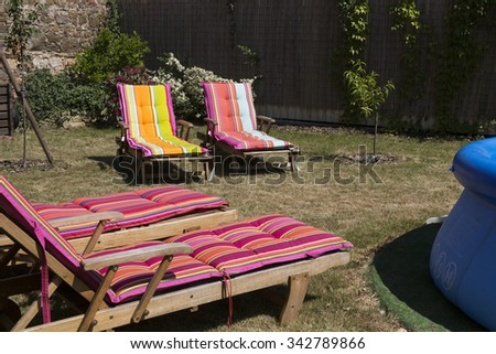 Four lawn chairs on the sun-drenched garden with colorful covers.. - stock photo