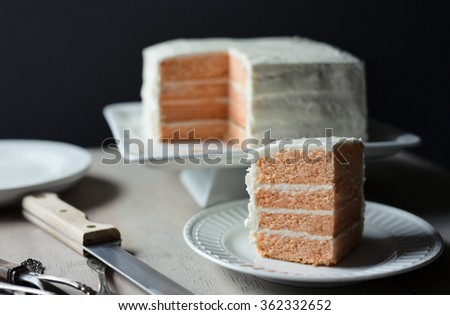 Four layer peach cake with vanilla frosting on a square white cake plate.