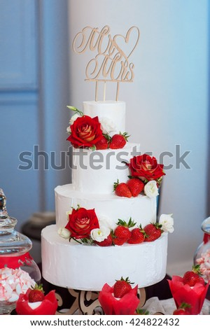 four-layer white wedding cake with red roses and strawberries - stock photo