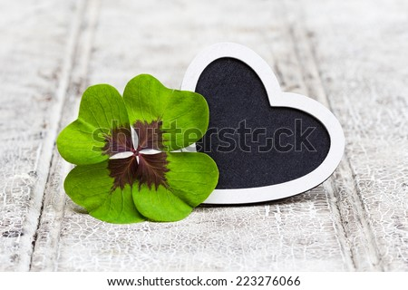 four leaf clover and heart on wood - stock photo