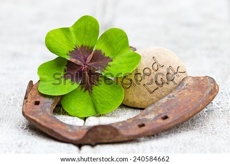 four leaf clover, horseshoe with stone and writing on wood, Good Luck - stock photo