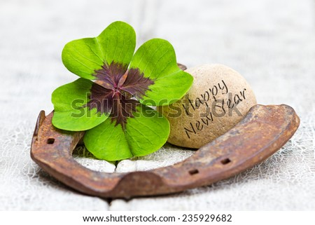 four leaf clover, horseshoe with stone and writing on wood, Happy New Year - stock photo