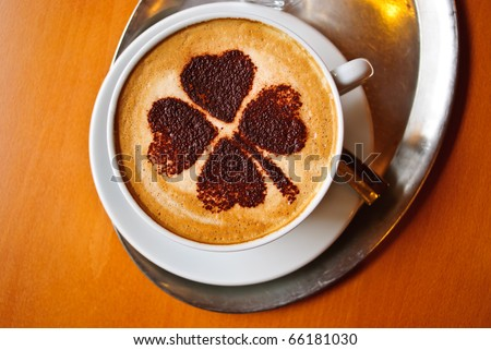 Four leaf clover shape on coffee in a cup - stock photo