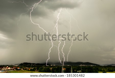 Four lightning bolts striking land during summer storm - stock photo