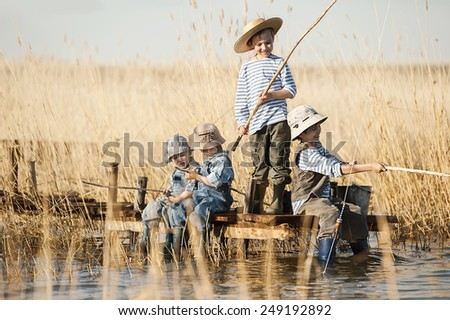 Four little boy is fishing at sunset on the lake - stock photo