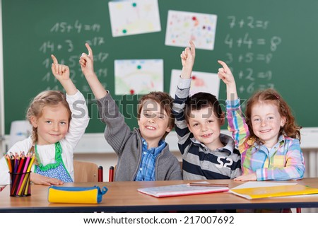 Four little schoolchildren raising their hands with excited expressions to show they know the answer to a question, two girls and two boys sitting in a row at a desk - stock photo