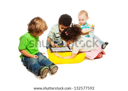 Four little two, and five years old kids playing with tablet computer, isolated on white