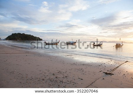 four long tail boat is sunset in andaman sea - stock photo