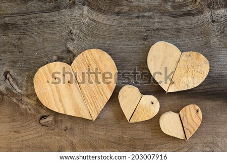 Four Love Valentines wooden hearts from recycled old palette on old grey Elm background, copy space