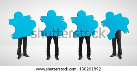 four man holding blue puzzle card - stock photo