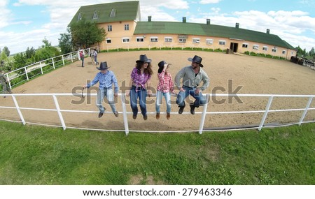 Four members family sit on fence near stable of ranch at summer sunny day. Aerial view - stock photo