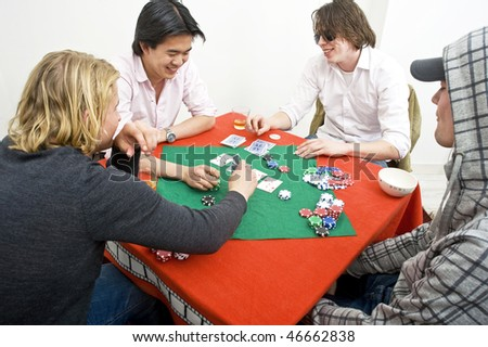 Four men playing a friendly game of backroom poker - stock photo
