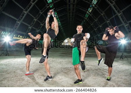 Four men practicing kick boxing, making hit with legs - stock photo