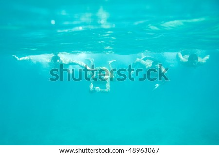 Four men swimming underwater in the sea - stock photo