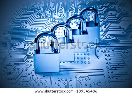 four metal locks on computer circuit board - computer security - stock photo