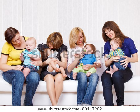 Four moms taking care of their children - stock photo