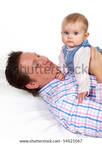 Four months old baby girl sitting on her father's belly - stock photo