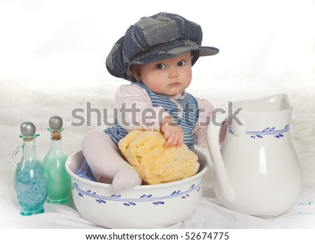 Four months old baby with cap in a wash basin with sponge