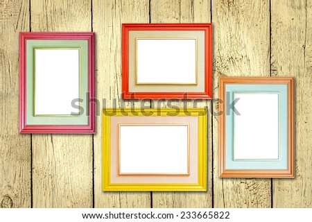 Four multicolored photo frames on the retro wood wall - stock photo