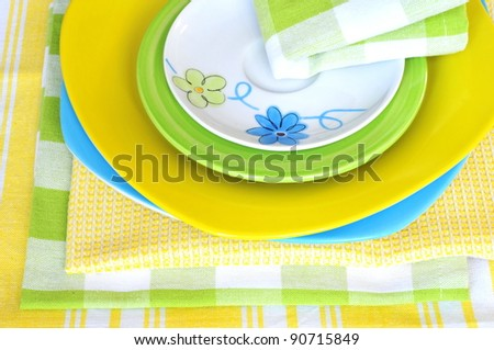 Four multicolored plates with napkins - stock photo