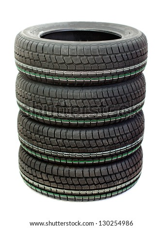 Four new tires stacked on one another on a white background - stock photo