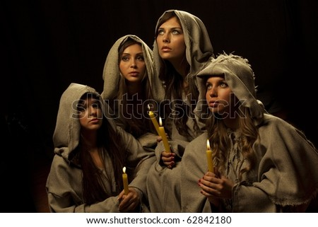 Four nuns praying with candles in their hands - stock photo