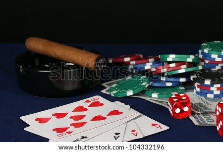 four of a kind on a blue poker table with dollars, playing cards and poker chips