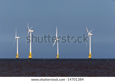 Four Offshore wind turbines in the North Sea. - stock photo
